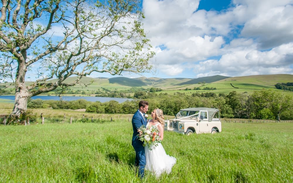 Bride and groom in long grass with Land Rover behind, Overwater Hall wedding, Lake District