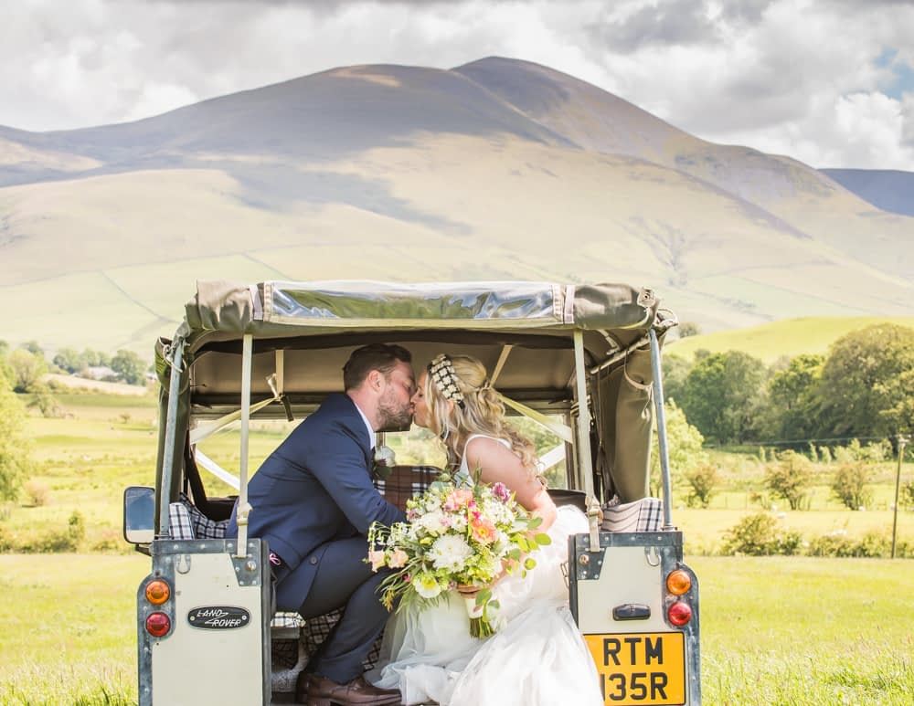 Kisisng in back of land rover, Overwater Hall wedding, Lake District