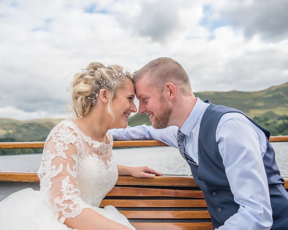 Looking at each other on boat, Inn on the Lake Weddings, Lake District