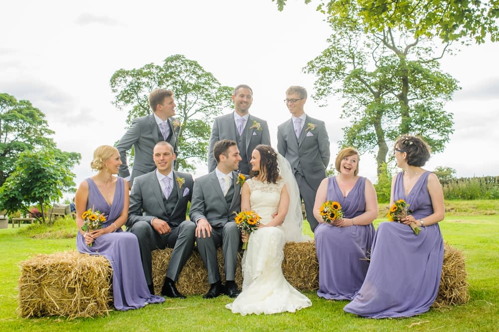 Bridal party portrait on hay bales, countryside wedding Lake District