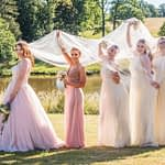 Bride and bridesmaids under veil in castle grounds, Ripley Castle weddings, Yorkshire wedding photographers