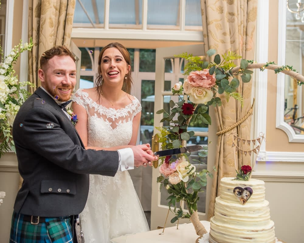 Laughing while about to cut the wedding cake, Sheffield wedding photographers, Ringwood Hall Hotel