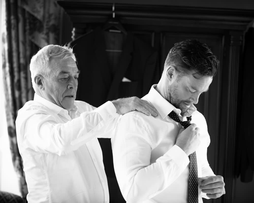 Groom's father putting Groom's tie on, Overwater Hall wedding, Lake District