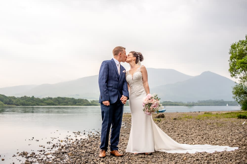Kim and Richard kissing by shore of Bassenthwaite Lake District wedding photographers