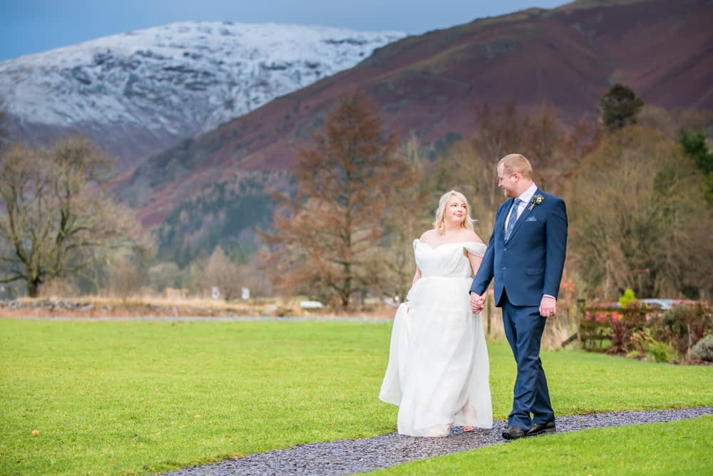 Walking through grounds with snowy mountains in the background, Daffodil Hotel weddings, Grasmere, Lake District wedding