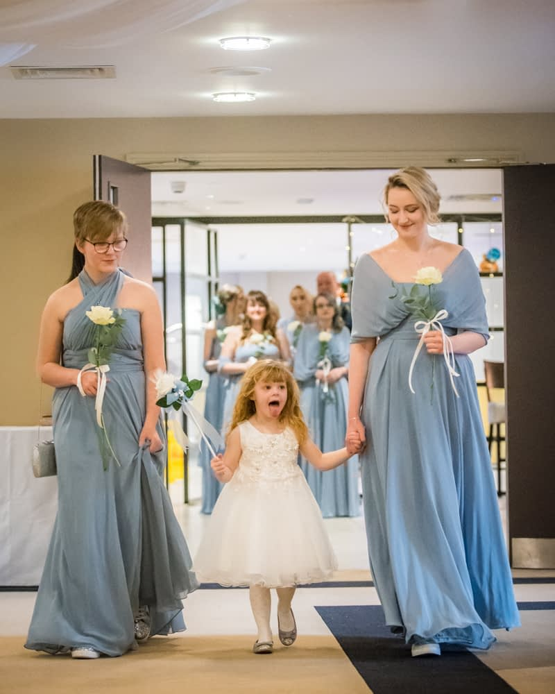 Bridesmaids walking down aisle, cheeky flowergirl sticking out tongue, Daffodil Hotel weddings, Grasmere, Lake District wedding