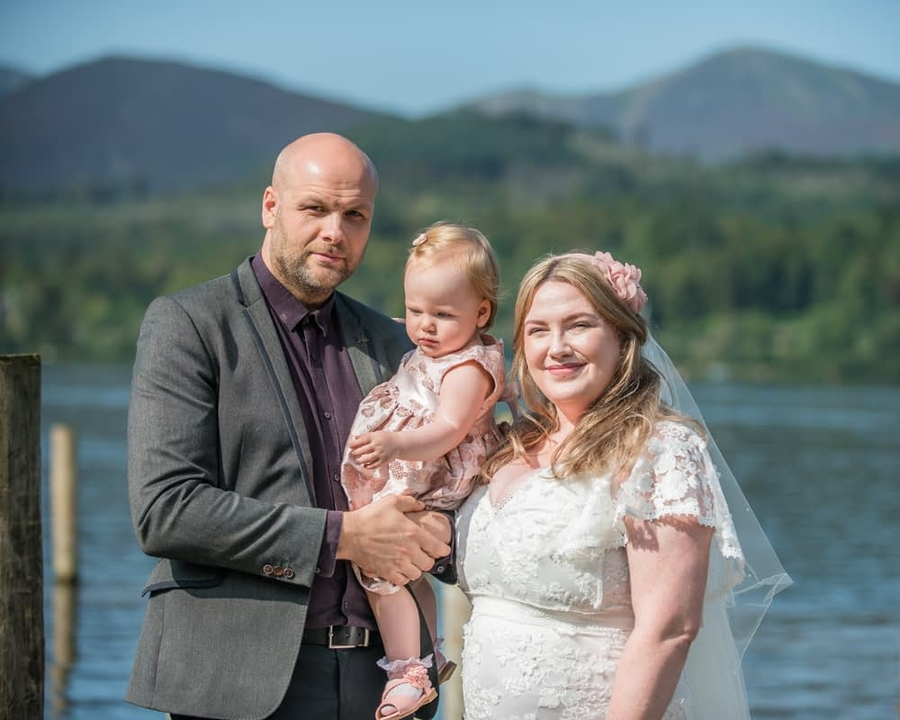Family posing by the lake, Derwentwater Rock the Dress, Lake District wedding photographer