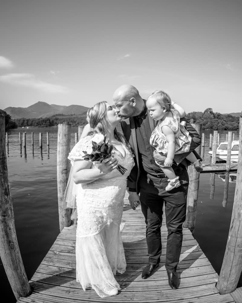 Kisses on jetty in Keswick, Derwentwater Rock the Dress, Lake District wedding photographer