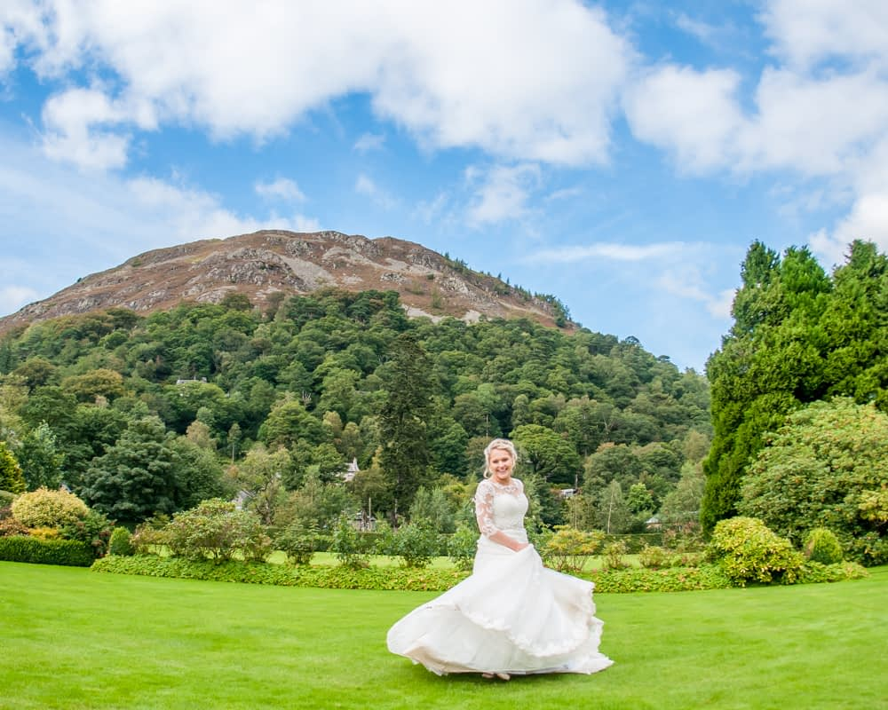 Bride twirling with fells in background, Inn on the Lake, Ullswater, Lake District documentary wedding photographers
