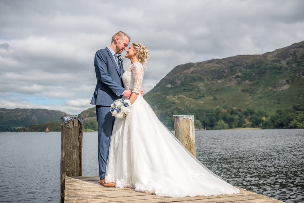 Bride and groom posing with fells in background, Inn on the Lake, Ullswater, Lake District documentary wedding photographers