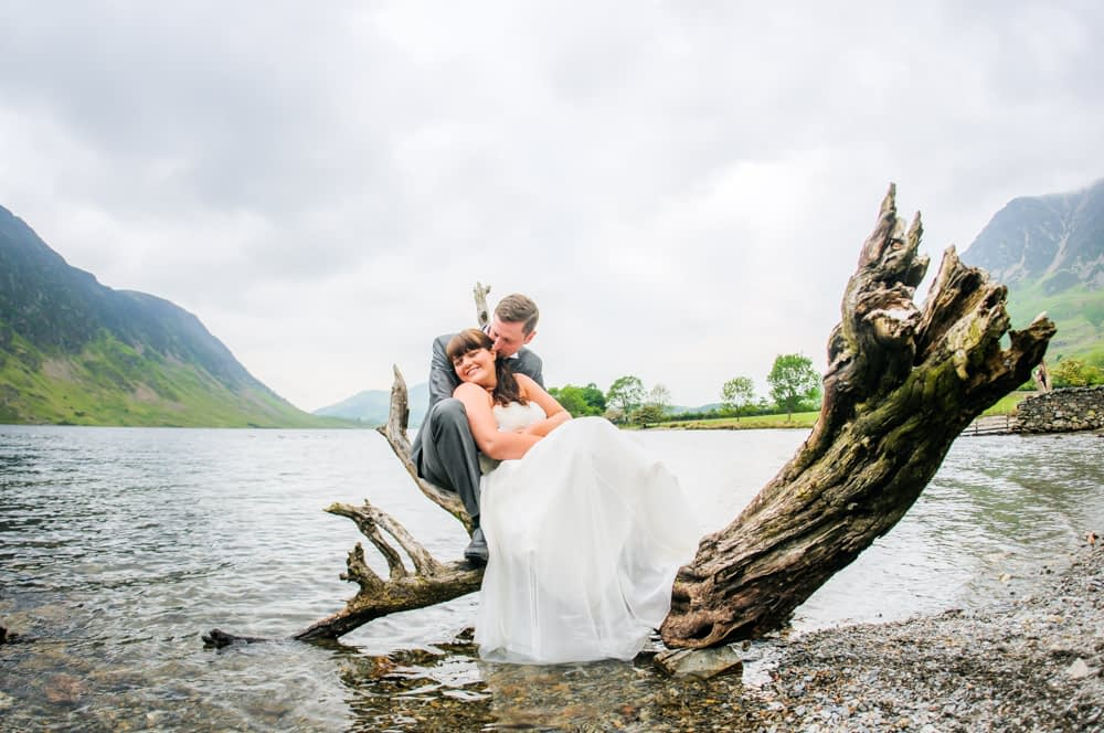 Bride and groom sat on driftwood in Crummock water, Broughton Craggs Hotel, wedding photographers Lake District