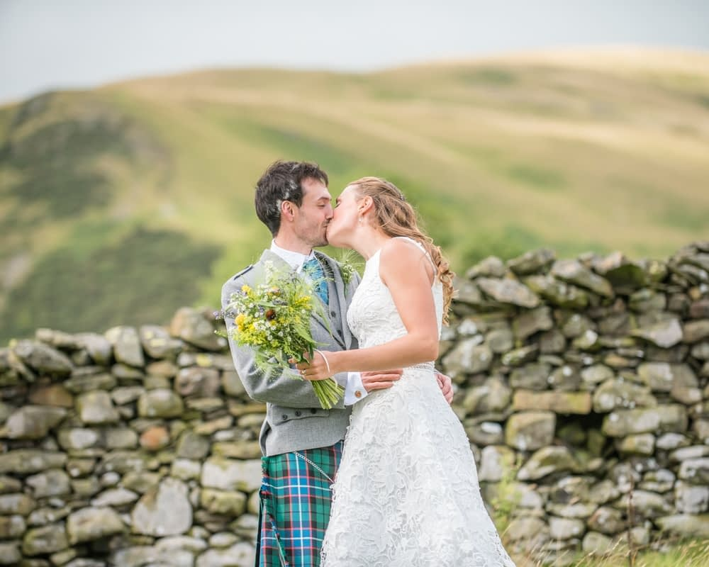Kisses with fell views, Howgills wedding, Sedbergh, Lake District wedding photographers