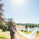 Bride and groom in the castle grounds with lake in background, Ripley Castle weddings, Yorkshire wedding photographers