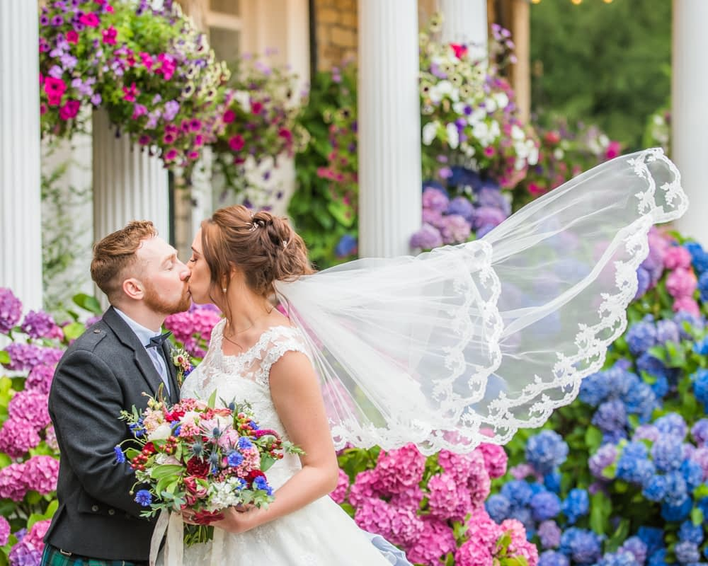 Brides veil blowing in breeze by flowers, Sheffield wedding photographers, Ringwood Hall Hotel