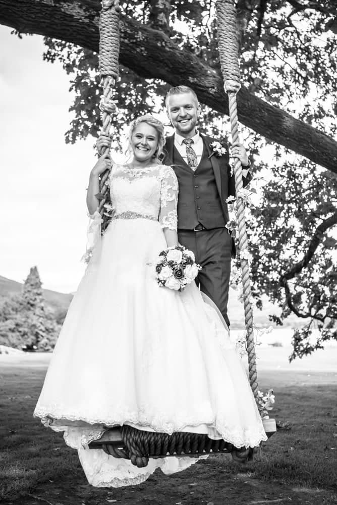 Happy couple squeezing onto the swing, Inn on the Lake Weddings, Lake District