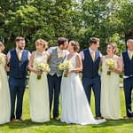 Bride and groom kissing with bridal party posing too, Ringwood Hall weddings, Sheffield wedding photographer