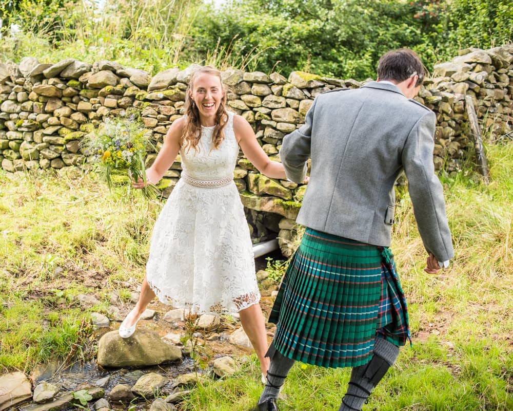 Bride jumping over stream, Sedbergh weddings, Lake District photography