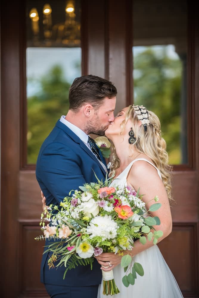 Kissing on steps of hall, Overwater Hall wedding, Lake District