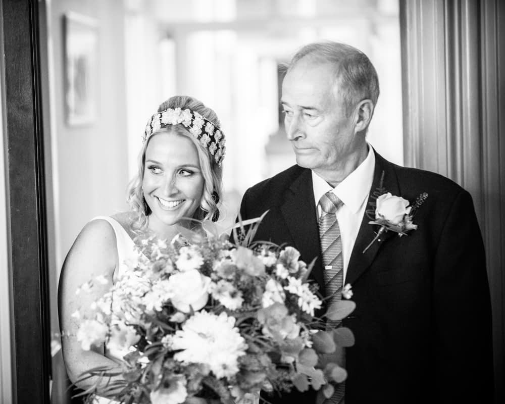 Bride and Dad peeking around ceremony door, Overwater Hall wedding, Lake District