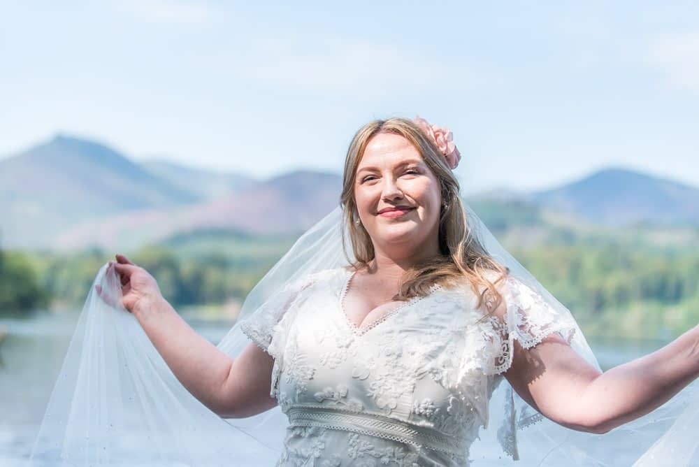 Holding out her veil, Derwentwater Rock the Dress, Lake District wedding photographer