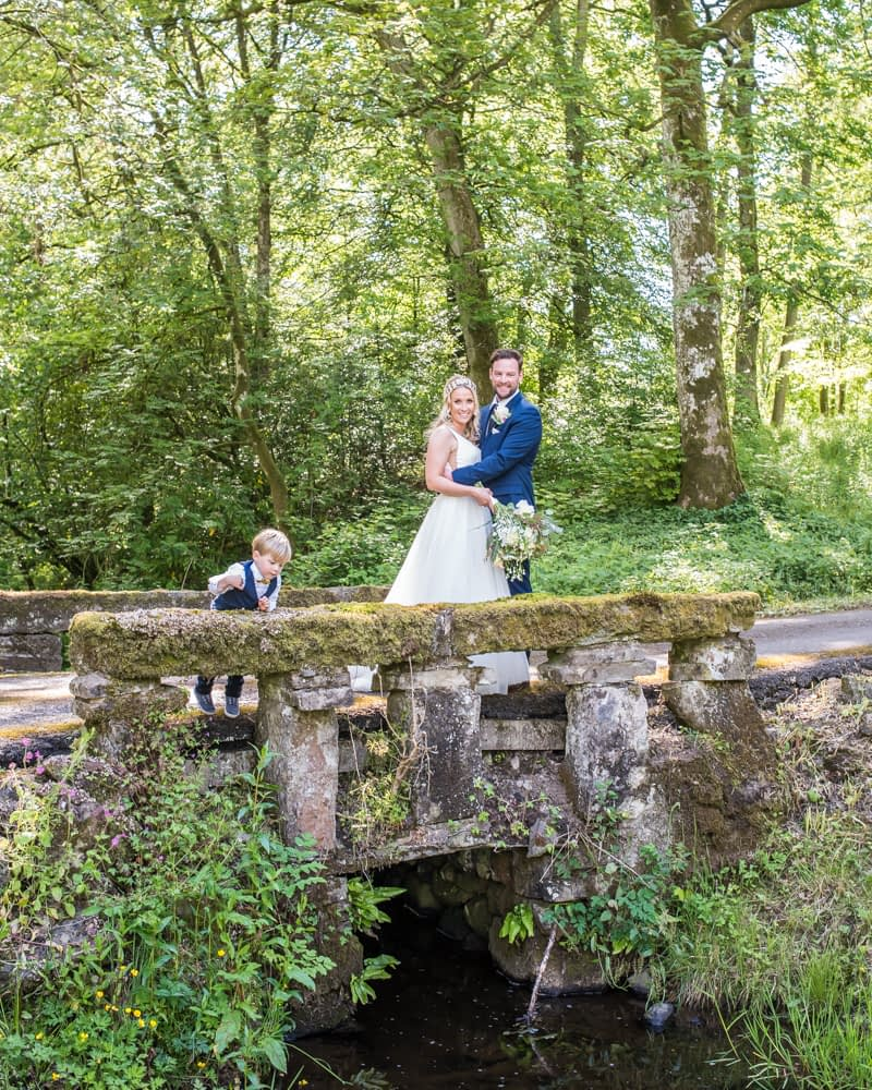 On the bridge with Callan throwing stones!Overwater Hall wedding, Lake District