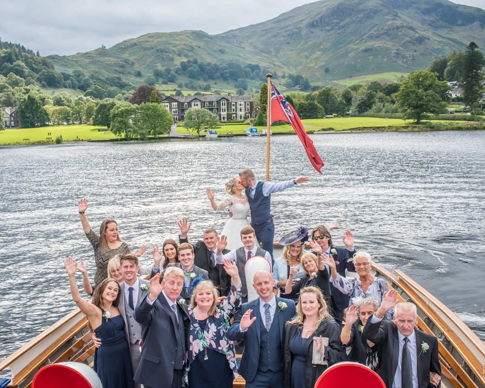 Posing on boat with hotel in background, Inn on the Lake Weddings, Lake District