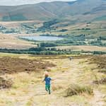 Boys running down Binsey with lake in background, Lake District photographers