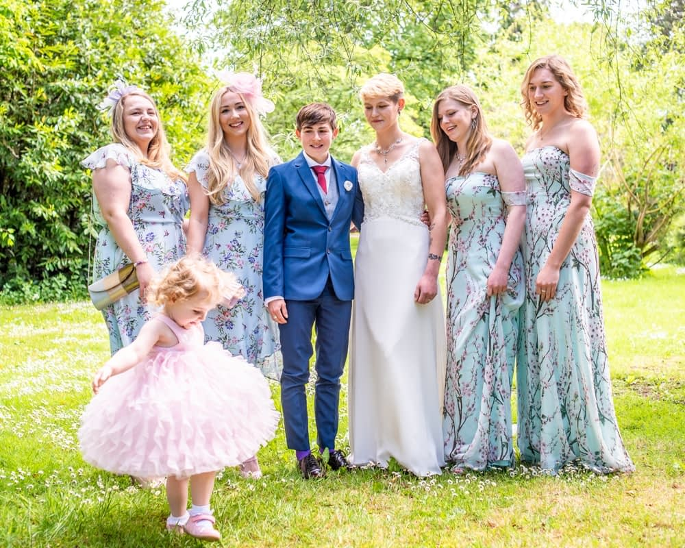 Flower girl showing off in group photo, Carlisle Register office, Lake District wedding photography