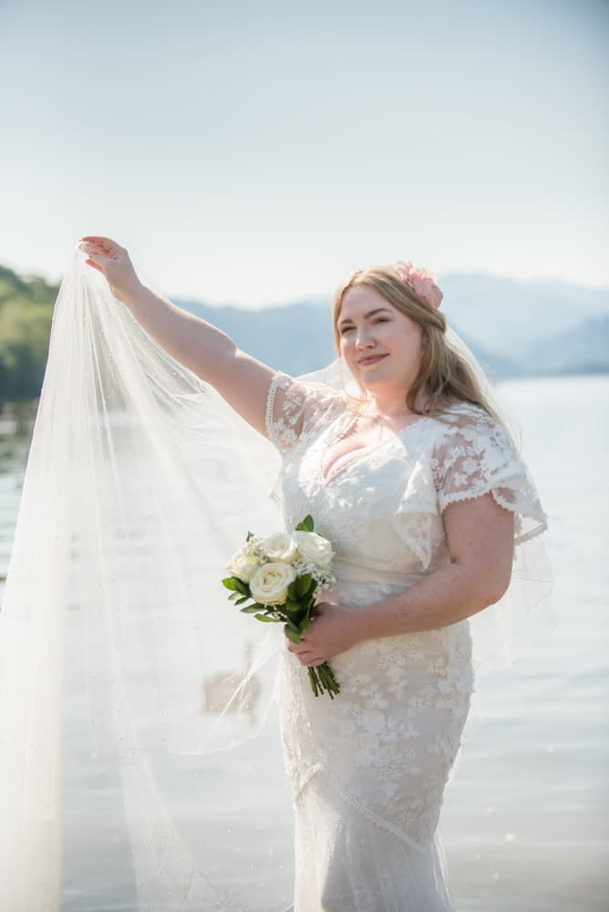 Bride holding out her veil. Derwentwater Rock the Dress, Lake District wedding photographer