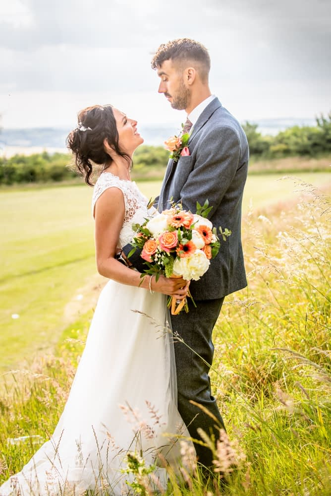 Bride and groom on playing field in the long grass, Sheffield weddings
