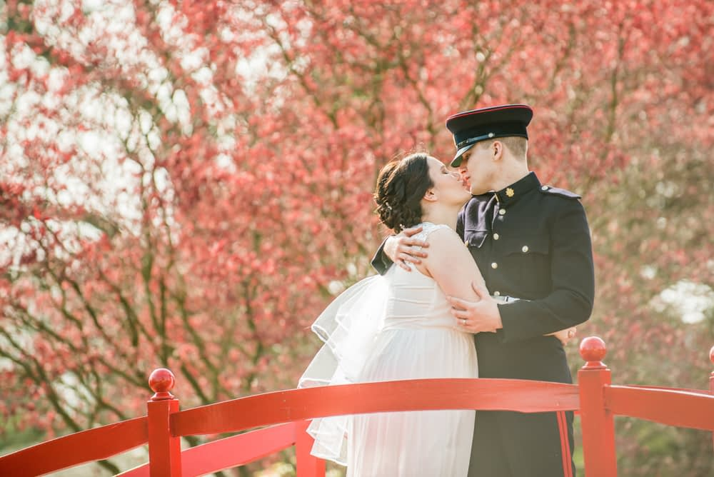 Kisses by red leaf trees in Water Gardens, military wedding, Greens at Gretna, Gretna Green Wedding photographers