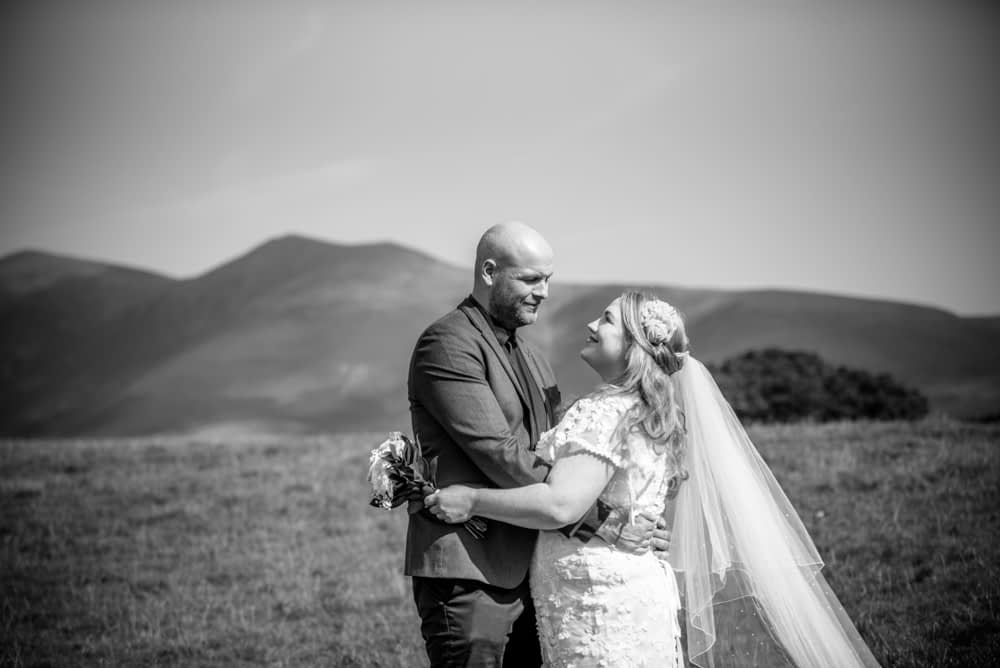 Bride and groom with fells in background, Derwentwater Rock the Dress, Lake District wedding photographer