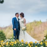 Bride and groom walking in daffodils, Whirlowbrook Hall wedding