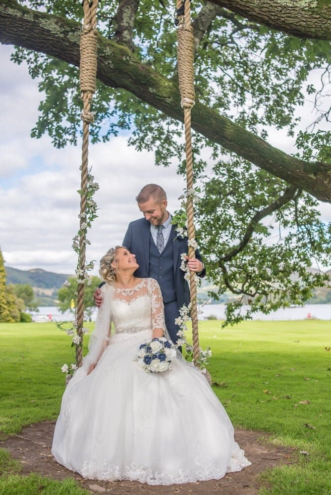 Bride on swing in hotel grounds, Inn on the Lake Weddings, Lake District