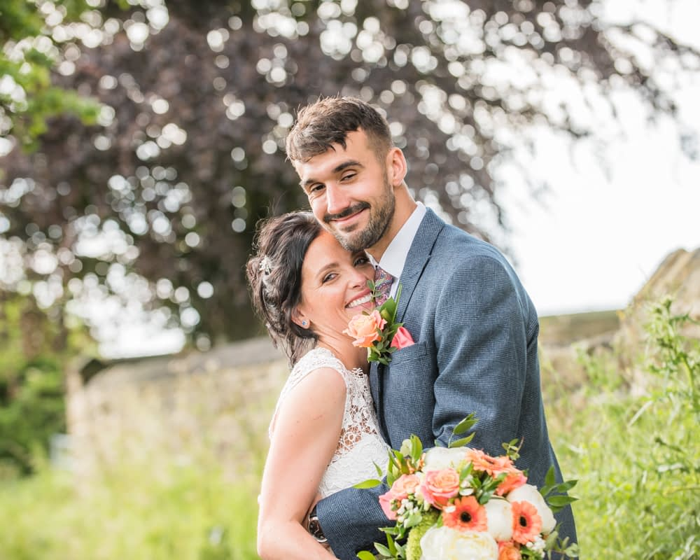 Cuddles for bride and groom on footpath, Barnsley weddings