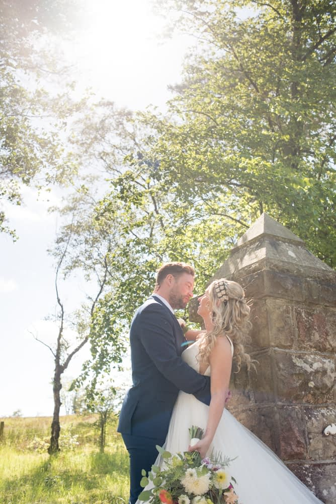 At the gates with sunshine flaring, Overwater Hall wedding, Lake District