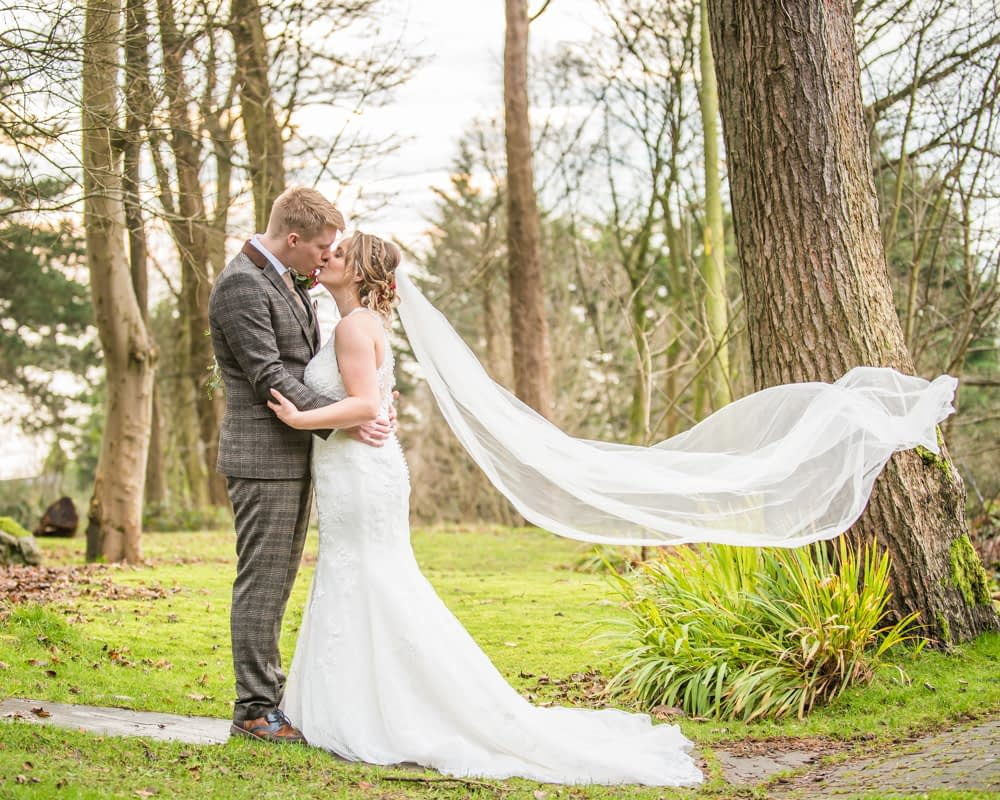 Bride and groom kissing in hotel grounds with veil blowing, Grange Hotel, Grange over Sands Lake District wedding photographers