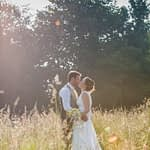 Bride and groom kissing in long grass at sunset, Ringwood Hall weddings, Sheffield wedding photographer