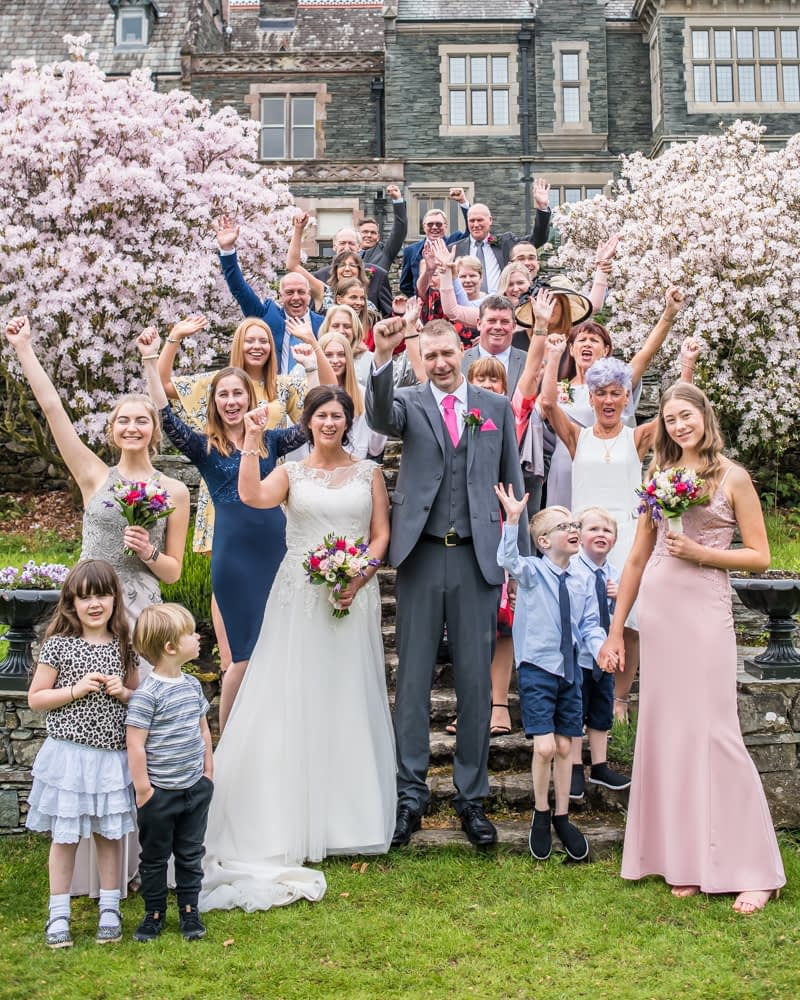 Full group photo waving, Lingholm wedding, Lake District
