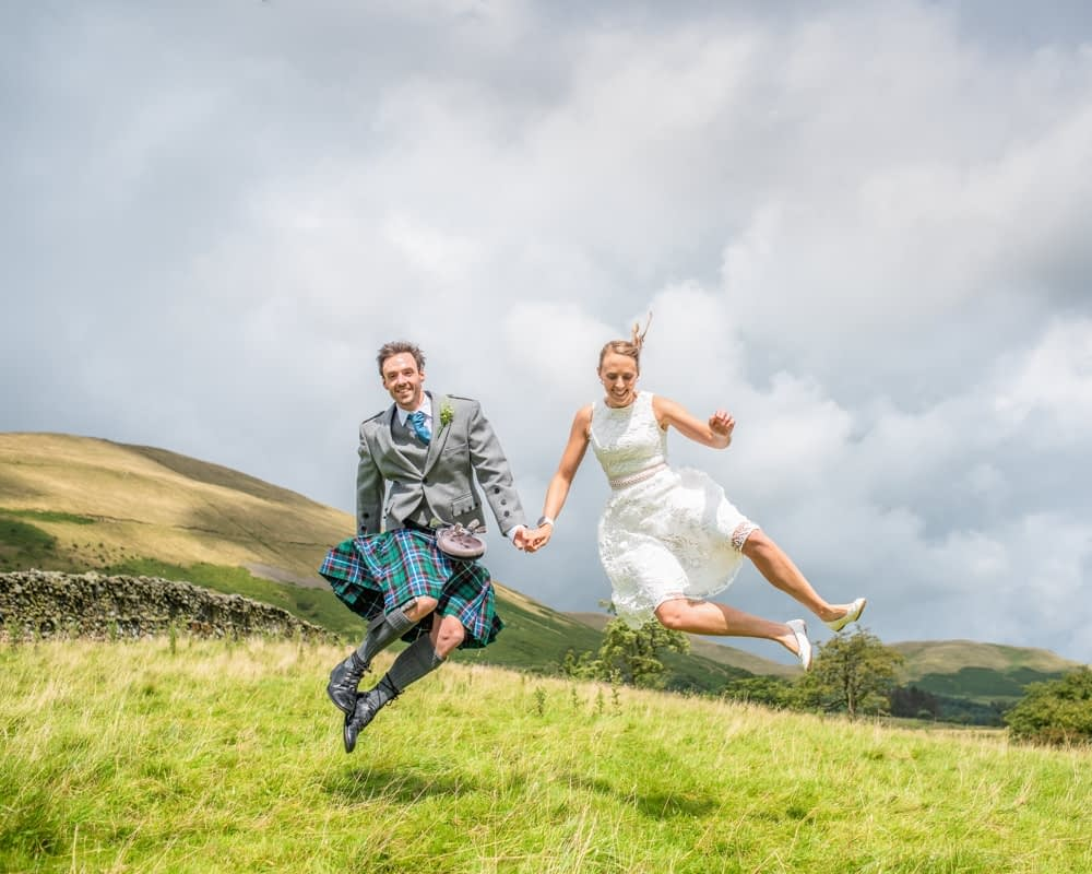 Doing a jump in the fields, Howgills wedding, Sedbergh, Lake District wedding photographers