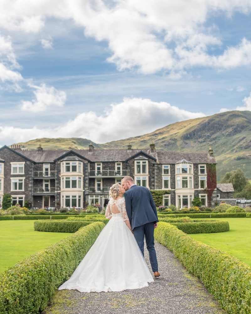 Kisses with hotel in background, Inn on the Lake Weddings, Lake District