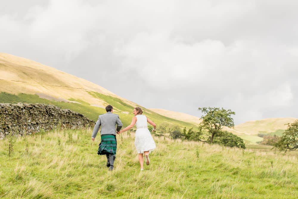 Bride and groom running through fields, Sedbergh weddings, Lake District photography