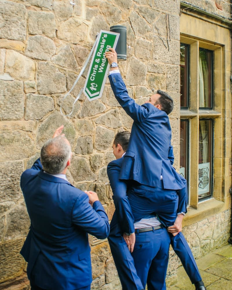 Groomsmen working out how to put sign up, Maynard wedding photography Sheffield