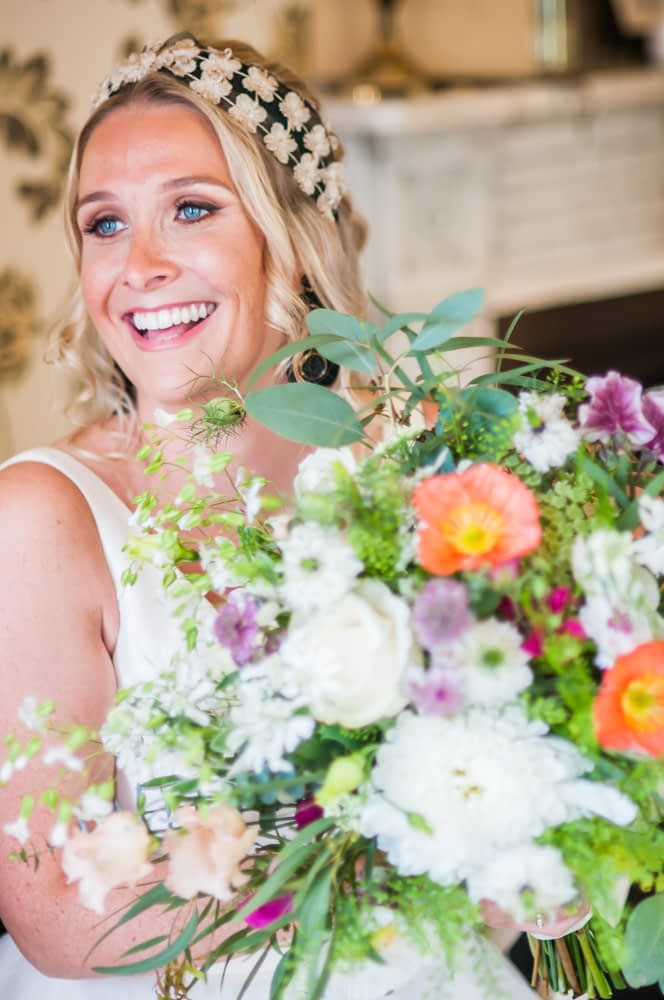 Bride laughing with her bouquet, Overwater Hall wedding, Lake District