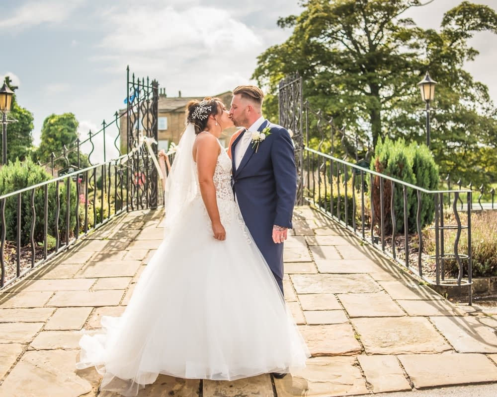 Kisses with bridge in the background, Waterton Park Hotel weddings, Yorkshire wedding photographers