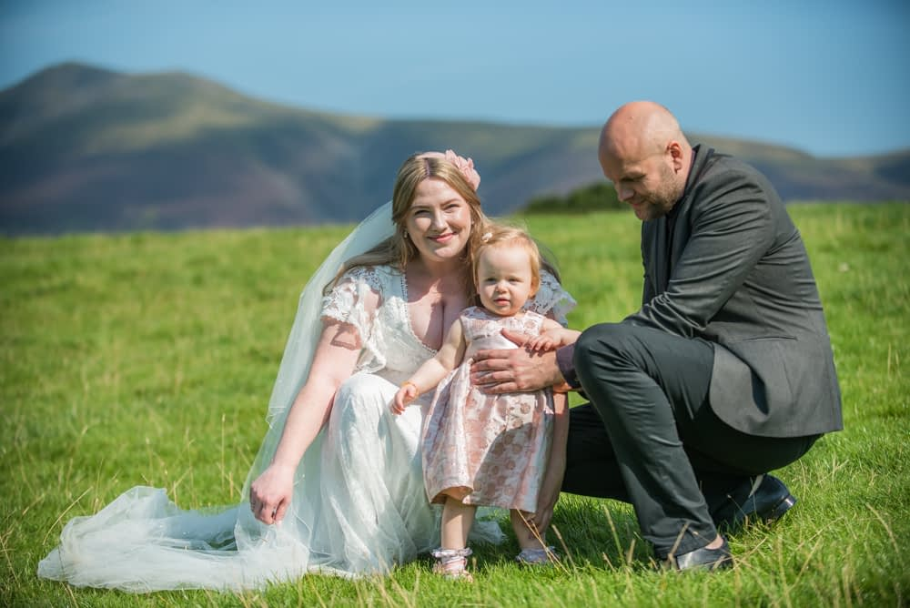 Cuddles with their daughter, Derwentwater Rock the Dress, Lake District wedding photographer