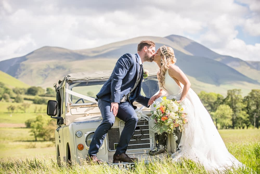 Kissing sat on Land Rover, Overwater Hall wedding, Lake District