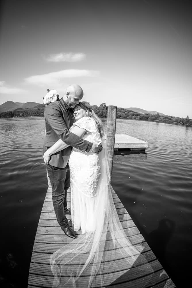 Snuggles for bride and groom, Derwentwater Rock the Dress, Lake District wedding photographer
