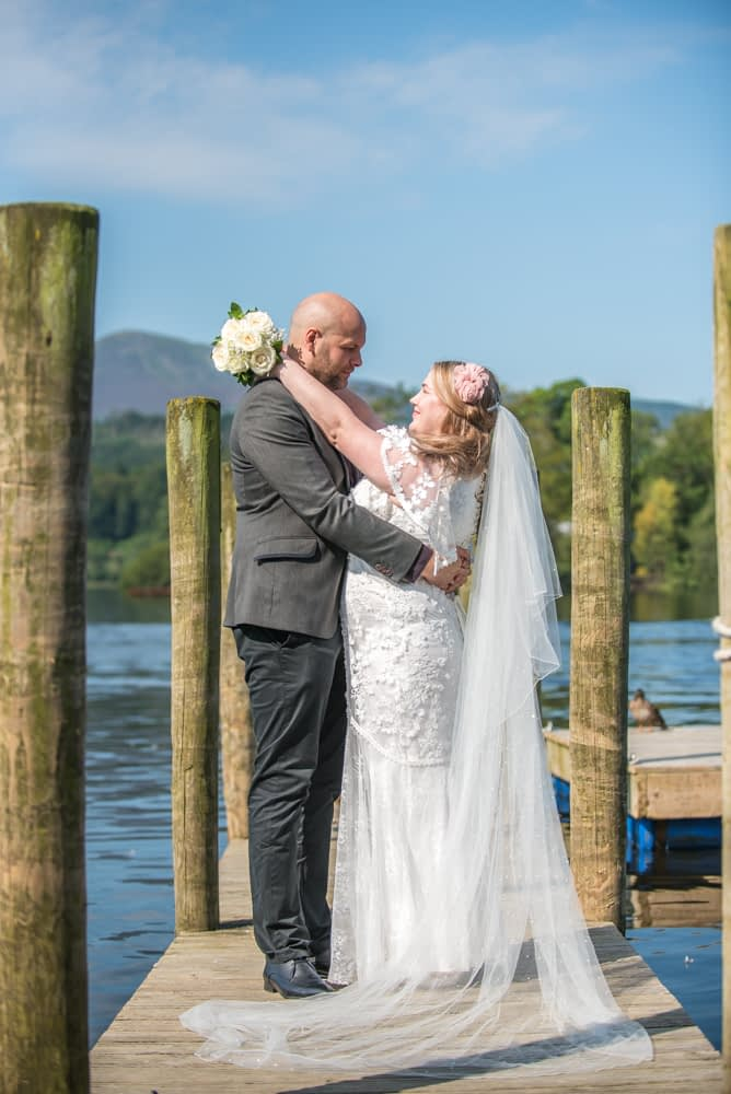 Laughing bride and groom on jetty, Derwentwater Rock the Dress, Lake District wedding photographer