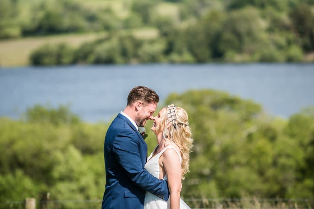 Smiling together with Overwater behind, Overwater Hall wedding, Lake District